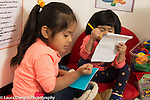 """Education Preschool 3 year olds two girls sitting near each other """"writing""""on pads of paper"""