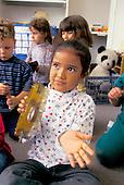 MR / Schenectady, New York.Yates Arts magnet School/ Pre-Kindergarten.Girl (4, Puerto-Rican and Ecuadorean-American) plays tambourine, as class uses rhythm instruments..MR: Lup1 .scan from slide.© Ellen B. Senisi