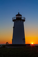 The rising sun adds color to the sky behind Edgartown Harbor Light in Edgartown, Massachusetts on Martha's Vineyard.