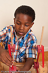 6 year old boy playing with wood stick and cube construciton kit vertical