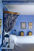 In this bedroom a glamorous note is created by a gilded antique canopy and blue and white floral bed hangings