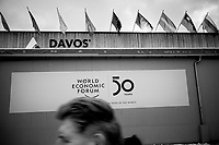 """Switzerland. Canton Graubunden. Davos. A sign on the Congress Center celebrates the 50th edition of the World Economic Forum (WEF). A man walks-by A man walks-by the Congress Center. Various flags: Italy, USA, Switzerland, Europe, United Nations, Austria, Liechtenstein, Columbia, The World Economic Forum (WEF) Annual Meeting in Davos is the foremost creative force for engaging the world's top leaders in collaborative activities to shape the global, regional and industry agendas at the beginning of each year. It brings together 3,000 participants from around the world, and aim to give concrete meaning to """"stakeholder capitalism"""", assist governments and international institutions in tracking progress towards the Paris Agreement and the Sustainable Development Goals, and facilitate discussions on technology and trade governance. 19.01.2020 © 2020 Didier Ruef"""