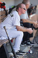 Charlotte Knights hitting coach Andy Tomberlin (11) escapes the heat in the shade of the dugout during the game against the Indianapolis Indians at BB&T BallPark on June 21, 2015 in Charlotte, North Carolina.  The Knights defeated the Indians 13-1.  (Brian Westerholt/Four Seam Images)