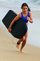 Girl (9-10) enthusiastically runs along beach with surfboard