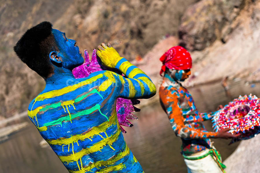 """A Cora Indian man, with body and face painted colorfully, paints his multi-colored hat before the spiritual ceremony of Semana Santa (Holy Week) in Jesús María, Nayarit, Mexico, 22 April 2011. The annual week-long Easter festivity (called """"La Judea""""), performed in the rugged mountain country of Sierra del Nayar, merges indigenous tradition (agricultural cycle and the regeneration of life worshipping) and animistic beliefs with the Christian dogma. Each year in the spring, the Cora villages are taken over by hundreds of wildly running men. Painted all over their semi-naked bodies, fighting ritual battles with wooden swords and dancing crazily, they perform demons (the evil) that metaphorically chase Jesus Christ, kill him, but finally fail due to his resurrection. La Judea, the Holy Week sacred spectacle, represents the most truthful expression of the Coras' culture, religiosity and identity."""