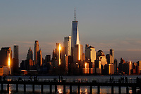 NEW JERSEY, HOBOKEN - FEBRUARY 27: People take a look of One World Trade Center and the New York skyline during a sunset on February 27, 2021 in Hoboken. New Jersey. New York City has seen an increase in leases signed since the 2008 financial crisis, only in Manhattan the increase was 58%, with 6,255 leases signed during the year. (Photo by Emaz/VIEWpress via Getty Images)