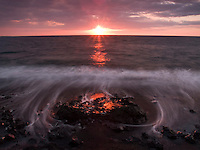 Water caresses lava rock as it flows back toward the sunset, North Kohala, Big Island.