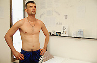 Switzerland. Bern. Regionalfgefängnis. Jail. Detention awaiting trial (commital for trial or pending trial). Loss of liberty. A prisoner Mr. D. N., stripped to the waist, stands up in his cell. Drawings and images are taped on the wall. Model Released. © 2005 Didier Ruef