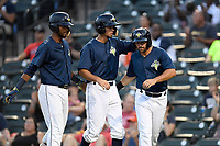 Second baseman Luis Carpio (11) of the Columbia Fireflies, left, congratulates Jacob Zanon and J.J. Franco after they both scored in a game against the Charleston RiverDogs on Monday, August 7, 2017, at Spirit Communications Park in Columbia, South Carolina. Columbia won, 6-4. (Tom Priddy/Four Seam Images)