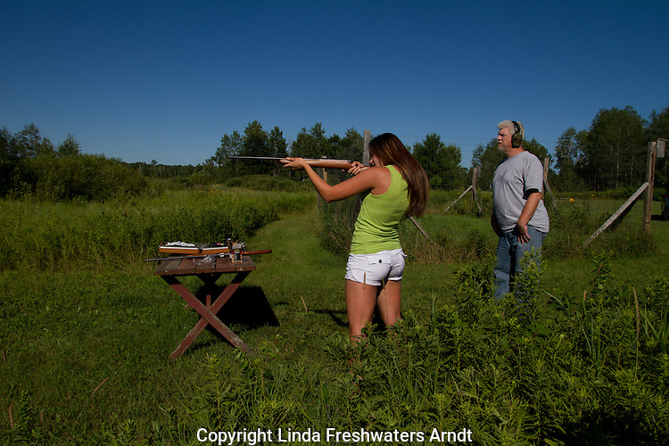 Young woman learning how to shoot a rifle