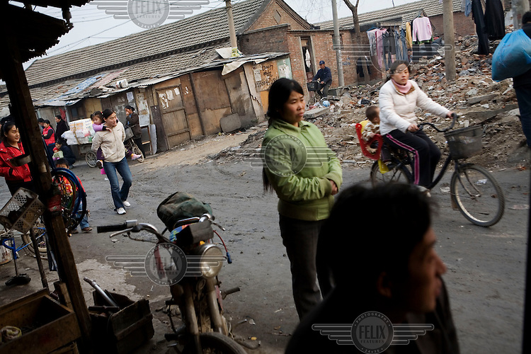 People living in a traditional 'hutong'. Many 'hutong' villages are being destroyed within Beijing to make way for new developments. Several new hotels, and a new golf course, are going to replace this particular 'hutong'. The people within these communities are due compensation, but it is likely that they will never receive any money due to corruption by local officials.