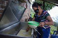ARMENIA - COLOMBIA, 29-05-2021: Martha Patiño cuela el queso para extraer el suero que se produce durante el proceso, este líquido que sobra es utilizado para alimentar a los cerdos. A más de un mes del inicio del Paro Nacional, los campesinos han tenido que reinventar la forma para mantener sus cultivos y criaderos activos para minimizar las pérdidas por los bloqueos que aún se mantienen en las vías. Según cifras del Ministerio de Hacienda, las pérdidas diarias están en un monto de $480.000 millones de pesos colombianos, lo cual sumando la totalidad de los días del Paro Nacional, suman un total de $10,8 billones de pesos colombianos. / Martha Patiño strains the cheese to extract the whey that is produced during the process; this leftover liquid is used to feed the pigs. More than a month after the beginning of the National Strike, farmers have had to reinvent ways to keep their crops and farms active to minimize losses due to the road blockades that are still in place. According to figures from the Ministry of Finance, the daily losses are in the amount of $480,000 million Colombian pesos, which adding all the days of the National Strike, add up to a total of $10.8 billion Colombian pesos. Photo: VizzorImage / Santiago Castro / Cont
