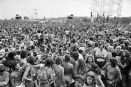 """Watkins Glen, NY. July, 1973.<br /> People sitting in the crowd at the Summer Jam at Watkins Glen was a 1973 rock festival which once received the Guinness Book of World Records entry for """"Largest audience at a pop festival."""" An estimated 600,000 rock fans came to the Watkins Glen Grand Prix Raceway outside of Watkins Glen, New York on July 28, 1973, to see The Allman Brothers Band, Grateful Dead and The Band perform.<br /> Similar to the 1969 Woodstock Festival, an enormous traffic jam created chaos for those who attempted to make it to the concert site. Long and narrow country roads forced fans to abandon their vehicles and walk 5–8 miles on that hot summer day. 150,000 tickets were sold for $10 each, but for all the other people it was a free concert. The crowd was so huge that a large part of the audience was not able to see the stage; however, twelve huge sound amplifiers, installed courtesy of legendary promoter Bill Graham, allowed the audience to at least hear."""