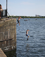 Saturday July 26th 2014 <br /> Pictured: Cardiff Bay <br /> RE: Men jump into the water at Cardiff Bay during the heat wave, one man wearing socks