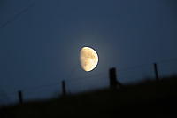 The moon rises over a farm fence in Llangammarch Wells, mid Wales, UK