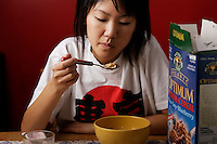 Montreal,  CANADA - Model Released  Illustration Photo - Asian  Girl eats cereals and a orange with juice for breakfast.<br /> <br /> <br /> Photo :  Agence Quebec Presse - Pierre Roussel