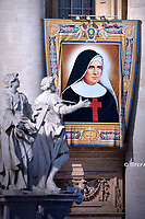 tapestry portraying Giuseppina Vannini, hangs from the facade of St. Peter's Basilica, at the Vatican. Pope Francis during  Canonization Mass for English John Henry Newman, Italian Giuseppina Vannini, Indian Maria Teresa Chiramel Mankidiyan, Brazilian Dulce Lopes Pontes, and Swiss Margarita Bays on October 13, 2019 In Saint Peter's square at the Vatican.
