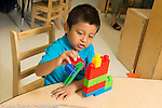 Education Preschool 4-5 year olds boy talking and playing using colorful construction as a vehicle or play piece