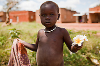 A young child picking flower blossoms in Madi Opei, Uganda.