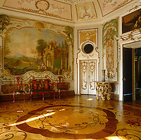 Russian painted chairs and a matching canape beneath a painted panel depicting a classical landscape in this rococo salon