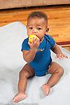 8 month old baby boy sitting biting toy