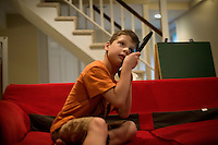 """Jack Ursitti looks at photos and listens to music on an iPad during a """"sensory break"""" in his home in Dover, Mass., on Monday, July 25, 2011.  Jack has been diagnosed with autism.  After school at his home, Jack works with his teacher and a therapist to do educational and independent leisure activities. Periodically Jack takes """"sensory breaks"""" to stop activity and play independently, allowing him to return to his tasks with greater concentration. During the """"sensory breaks"""" Jack does a variety of things, including looking at his reflection, making faces, jumping on a small trampoline or cushions, or play with an iPad...Jack Ursitti wears a small GPS ankle bracelet at all times in case he runs off from his family or caretakers. The device will be activated if he goes missing, allowing police and other searchers to find him."""