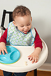 9 month old baby boy closeup in highchair wearing bib feeding self finger food