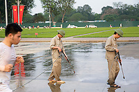 Vietnam. Hanoi. Ho Chi Minh's Mausoleum. A man runs while two workers, both wearing green vietnamese army helmets, are using pressure washers. Pressure washers are mechanical devices that uses high-pressure water to remove mold, grime, dust, mud and dirt from surfaces and objects such as concrete road surfaces. Flag of Vietnam (L), also known as the red flag with yellow star. The red symbolises the revolution and the blood shed in the struggle for independence. The five-pointed yellow star represents the unity of workers, peasants, intellectuals, traders and soldiers in building socialism. Flag of the Vietnamese Communist Party (R) with hammer and sickle.  04.04.09 © 2009 Didier Ruef