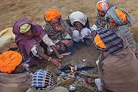A group of camel traders light fire early in the morning to warm themselves. Pushkar, Rajasthan, India.