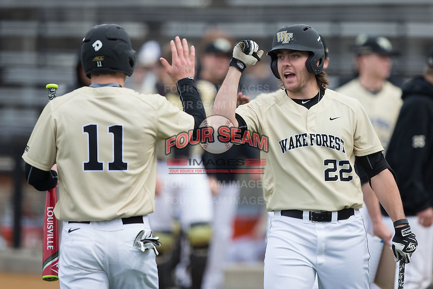 Will Craig (22) of the Wake Forest Demon Deacons congratulates teammate Jonathan Pryor (11) after he scored a run against the Harvard Crimson at David F. Couch Ballpark on March 5, 2016 in Winston-Salem, North Carolina.  The Crimson defeated the Demon Deacons 6-3.  (Brian Westerholt/Four Seam Images)