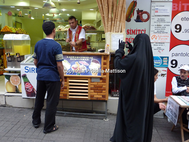 Istanbul, Turkey - September 25, 2009:  A woman wearing a burka and gloves photographs a man being served at an ice cream stand.