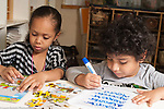Education preschool 3-4 year olds girl playing with puzzle next to boy tracing or writing letters of his name