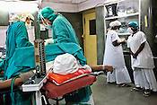 Government nurse (right) undergoing training look over the shoulder of a surgeon who operates a caesarean section on a woman at the operation theatre in Duncan Hospital in Raxaul of East Champaran district of Bihar, India. Since 2008 the Foundation and Geneva Global have been investing in the training of medical staff to improve the lives of people living in 600+ villages in the region. The NGOs are delivering cost effective interventions to address treatment, care and prevention of diseases, disability and preventable deaths amongst infants, adolescent girls and women of child-bearing age. There is statistical and anecdotal evidence that there have been vast improvements and a total of 40-50% increased immunization for all children under 6 has meant that communities can be serviced and educated long term. Photograph: Sanjit Das/Panos for Legatum Foundation