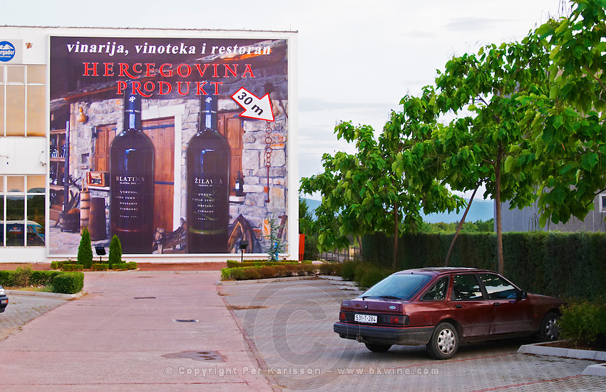 Advertising poster billboard on the outside of the winery. Car in the parking lot. Hercegovina Produkt winery, Citluk, near Mostar. Federation Bosne i Hercegovine. Bosnia Herzegovina, Europe.