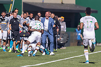 Portland, Oregon - Sunday October 6, 2019: Larrys Mabiala celebrates scoring the first goal of the game by tackling Claude Dielna #5 on the sideline while Timbers Head Coach, Giovanni Savarese, looks on during a regular season match between Portland Timbers and San Jose Earthquakes at Providence Park in Portland, Oregon.