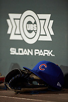 A Chicago Cubs hat rests on a baseball glove during an Arizona League game between the AZL Giants Orange and AZL Cubs 1 on July 10, 2019 at Sloan Park in Mesa, Arizona. The AZL Giants Orange defeated the AZL Cubs 1 13-8. (Zachary Lucy/Four Seam Images)
