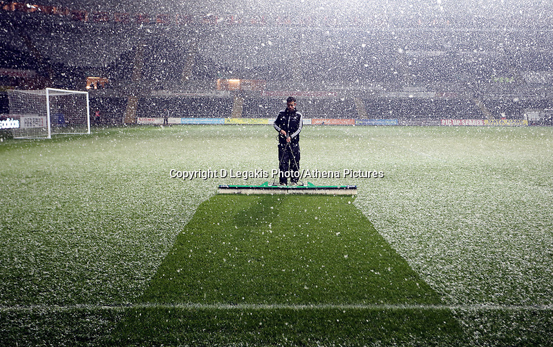 Wednesday 23 January 2013<br /> Pictured: A Swansea City FC groundsman is brushing the snow away.<br /> Re: Capital One Cup semi-final second leg, Swansea City FC v Chelsea at the Liberty Stadium, south Wales.