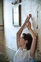 Young woman leaning against broken plaster wall with arms raised