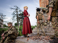Natalia Voronkova, a volunteer who offers support and basic first aid training for Ukrainian government forces fighting Russian-backed separatists in the east of the country, with a group of soldiers at the entrance to a destroyed church in the frontline city of Pisky, located in the outskirts of Donetsk, the stronghold of the russian backed separatist. Not a single house in the town stands untouched by the war. According to the Ukranian govenment soldiers based here, not a day goes by without attacks from the separatist forces, either from snipers or shelling.