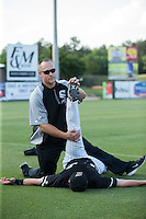 Kannapolis Intimidators conditioning coach Bret Kelly helps Grant Massey (16) stretch prior to the game against the Lakewood BlueClaws at Kannapolis Intimidators Stadium on May 10, 2016 in Kannapolis, North Carolina.  The BlueClaws defeated the Intimidators 5-3.  (Brian Westerholt/Four Seam Images)