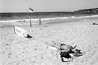 Australia. New South Wales. Coogee Beach. A topless woman lies on her back on the sand. She rests and gets a suntan. A lifeguard board is ready for any rescue. A man walks close to the shore of the Pacific Ocean. 14.3.99 © 1999 Didier Ruef