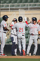 Kyri Washington (21) of the Greenville Drive is greeted by teammates Josh Ockimey (18), Tate Matheny (16), and Mitchell Gunsolus (22) after hitting a home run against the Kannapolis Intimidators at Intimidators Stadium on June 7, 2016 in Kannapolis, North Carolina.  The Drive defeated the Intimidators 4-1 in game one of a double header.  (Brian Westerholt/Four Seam Images)