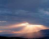 Sun rays breaking through a clearing storm; Dinosaur National Monument, CO