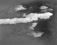 """""""Snow On The Driveway"""" <br /> <br /> Snow remaining on an asphalt driveway after melting had begun is shown in this black and white photograph."""
