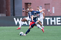 FOXBOROUGH, MA - JULY 4: Andrew Booth #19 of Greenville Triumph SC tries to intercept a shot on goal by Pierre Cacet #44 of the New England Revolution II during a game between Greenville Triumph SC and New England Revolution II at Gillette Stadium on July 4, 2021 in Foxborough, Massachusetts.