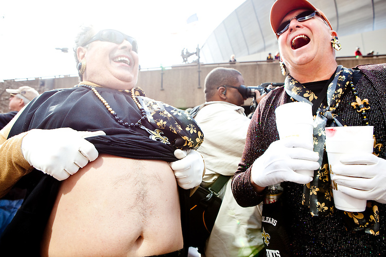 """A Saints fan pulls up his dress to show off the fleur de lis shaved into his stomach at the parade in Buddy D's honor on January 31, 2010 in New Orleans.<br /> <br /> Thousands of Saints fans wearing dresses paraded from the Louisiana Superdome to the French Quarter to honor a promise made by the late sportscaster and Saints super-fan Buddy Diliberto aka """"Buddy D"""".<br /> <br /> In 1993 Buddy D, who passed away in 2005, remarked on air that if the Saints were to make it to the Super Bowl, he would wear a dress and dance down the streets.  The comment was repeated at various times and never forgotten by his listeners.<br /> <br /> Led by former New Orleans Saints quarterback Bobby Hebert, who has taken Buddy D's place on WWL radio, thousands made good on his promise for him, dancing, drinking, and cavorting their way down the street, alternately yelling out """"Who Dat!"""" and """"Buddy D!"""" in front of an onlooking crowd an estimated 85,000 people strong.<br /> <br /> The hard luck NFL team the New Orleans Saints has reached its first Super Bowl in team history, after 43 years largely filled with losing seasons and futility.  It is difficult to travel anywhere in the area without some reminder of this fact, as the team and city are intertwined perhaps like no other sports franchise in this country."""