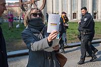 """Etwa 3 dutzend Menschen versuchten am Samstag den 28. Maerz 2020 in Berlin-Mitte, trotz einem allgemeinen Versammlungsverbot durch die Behoerden sich zu einer """"Hygienedemo"""" zu versammeln. Ihre Forderung war """"fuer unsere Verfassung, das Grundgesetz, sowie Transparenz, Pressefreiheit, Wahlen und vollstaendige Demokratie & Transparenz bei der Einsetzung neuer Wirtschaftsgesetze in Form einer """"Verfassung der Oekonomie"""".<br /> Es wurden Exemplare des Grundgesetz verteilt. Die Polizei forderte die Menschen auf sich zu zerstreuen und nach ca. 30 Minuten nahm sie von Menschen, die der Aufforderung nicht nachkamen die Personalien auf und erteilte Platzverweise.<br /> Aufgerufen zu der Aktion hatte eine Gruppe namens """"nichtohneuns.de"""".<br /> Im Bild: Eine Frau haelt ein Exemplar des Grundgesetz in den Haenden, im Hintergrund die Polizei.<br /> 28.3.2020, Berlin<br /> Copyright: Christian-Ditsch.de<br /> [NUR FUER REDAKTIONELLE ZWECKE! Werbung nur auf Anfrage beim Fotografen. Inhaltsveraendernde Manipulation des Fotos nur nach ausdruecklicher Genehmigung des Fotografen. Vereinbarungen ueber Abtretung von Persoenlichkeitsrechten/Model Release der abgebildeten Person/Personen liegen nicht vor. NO MODEL RELEASE! Don't publish without copyright Christian-Ditsch.de, Veroeffentlichung nur mit Fotografennennung, sowie gegen Honorar, MwSt. und Beleg. Konto: I N G - D i B a, IBAN DE58500105175400192269, BIC INGDDEFFXXX, Kontakt: post@christian-ditsch.de<br /> Bei der Bearbeitung der Dateiinformationen darf die Urheberkennzeichnung in den EXIF- und  IPTC-Daten nicht entfernt werden, diese sind in digitalen Medien nach §95c UrhG rechtlich geschuetzt. Der Urhebervermerk wird gemaess §13 UrhG verlangt.]"""