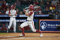 Robert Moore (1) of the Arkansas Razorbacks follows through on his swing against the Baylor Bears in game nine of the 2020 Shriners Hospitals for Children College Classic at Minute Maid Park on March 1, 2020 in Houston, Texas. The Bears defeated the Razorbacks 3-2. (Brian Westerholt/Four Seam Images)