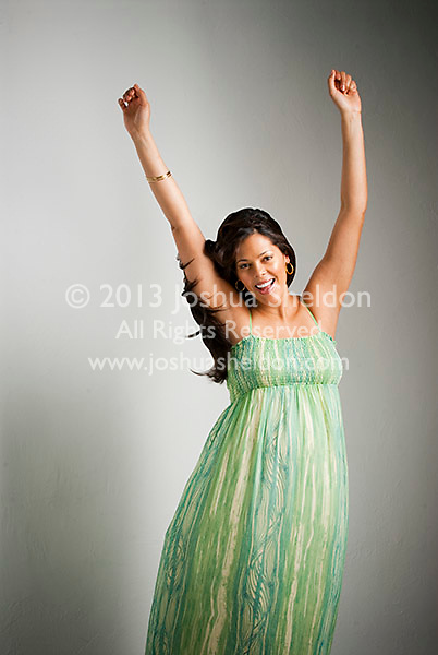 Pregnant Hispanic woman, hands in air