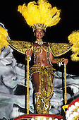 Rio de Janeiro, Brazil. Carnival; woman in ornate gold and black costume with feather headdress. Sapucai sambadrome.